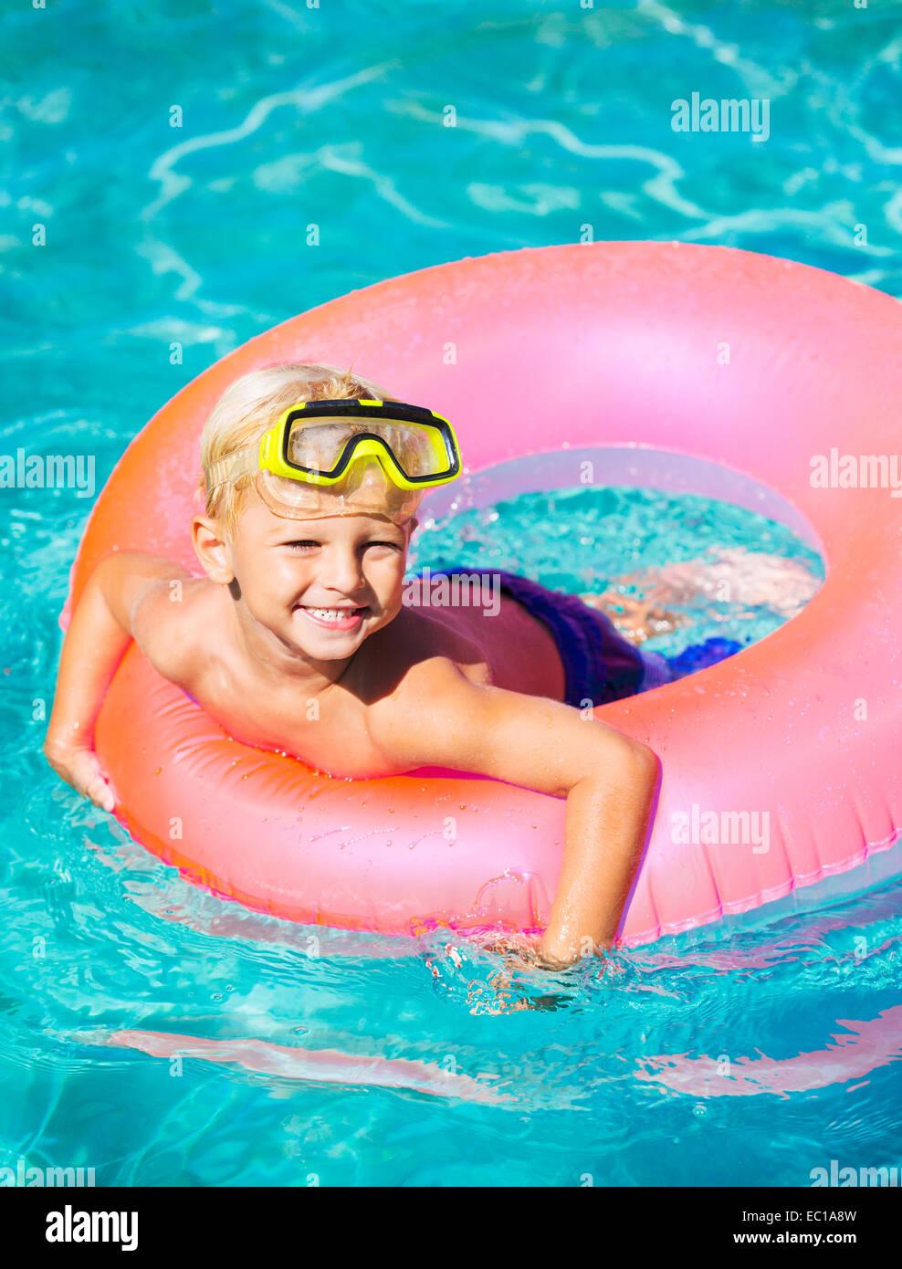 Feliz Joven flotando en una piscina en balsa Imagen De Stock