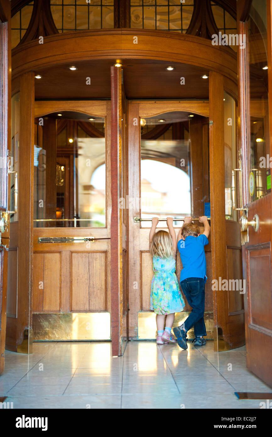Dos niños empujando una puerta giratoria en la entrada del hotel Imagen De Stock