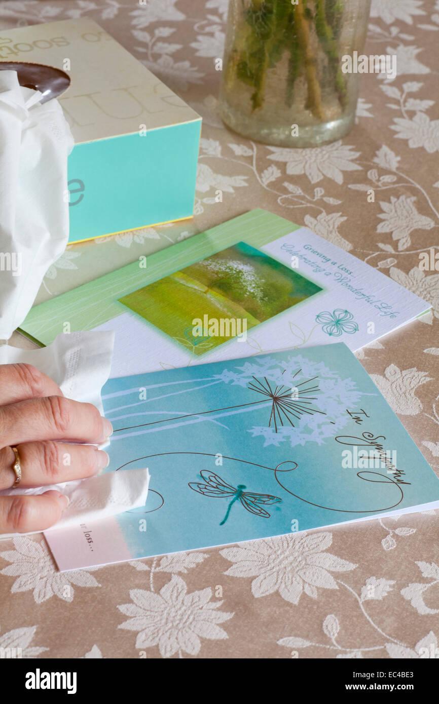 Mano sujetando el tejido con tarjetas de pésame y de la caja de pañuelos en un mantel. Imagen De Stock