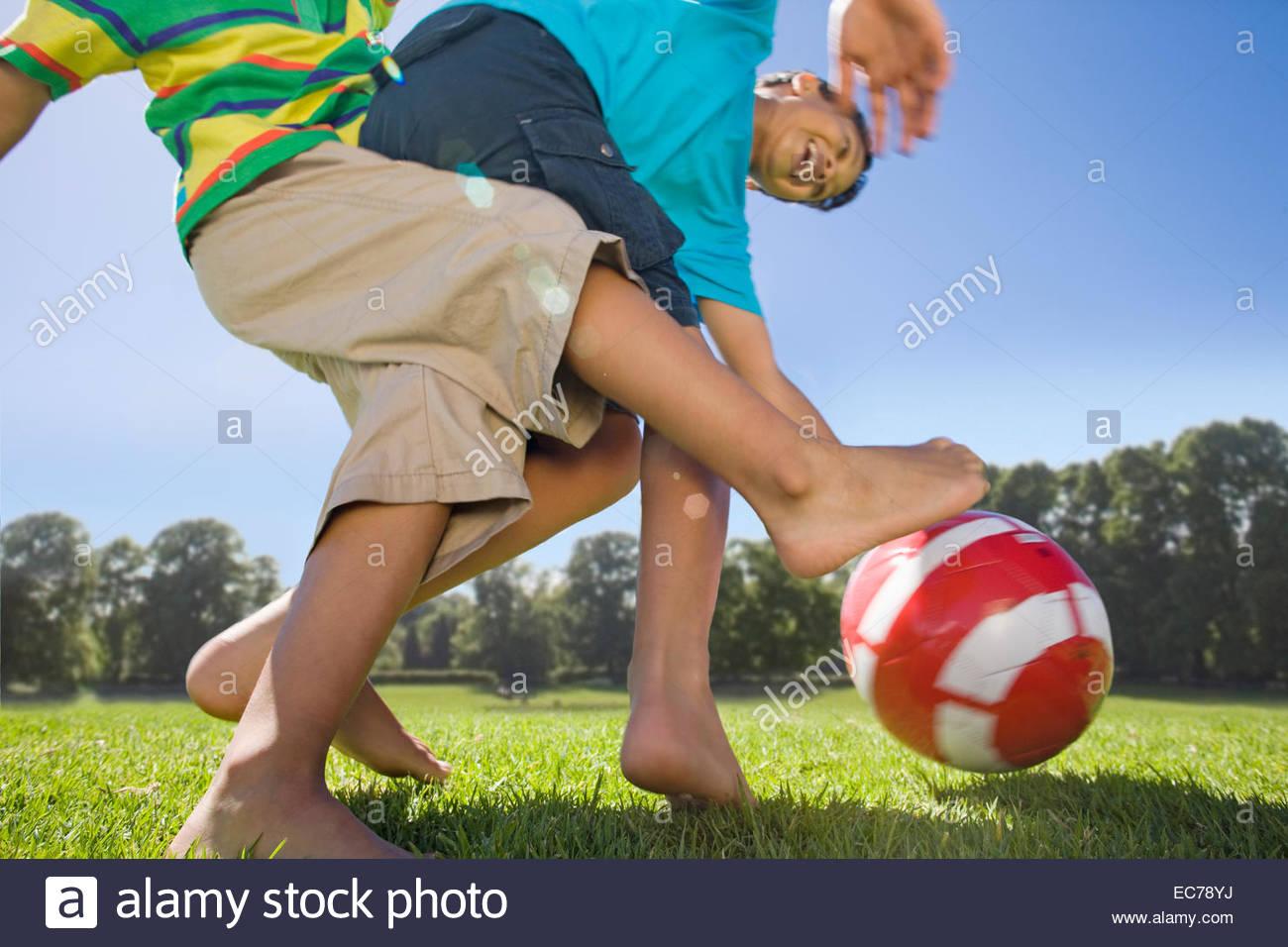 Sonrientes muchachos jugando al fútbol en el parque Imagen De Stock