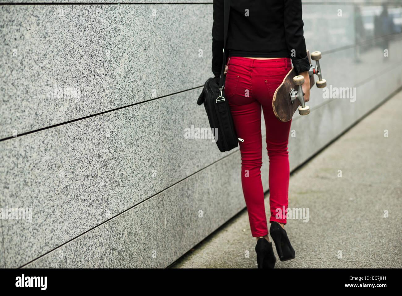 Mujer Joven Con Bolsa Y Skate Pantalones Vestidos De Rojo Vista Parcial Fotografia De Stock Alamy