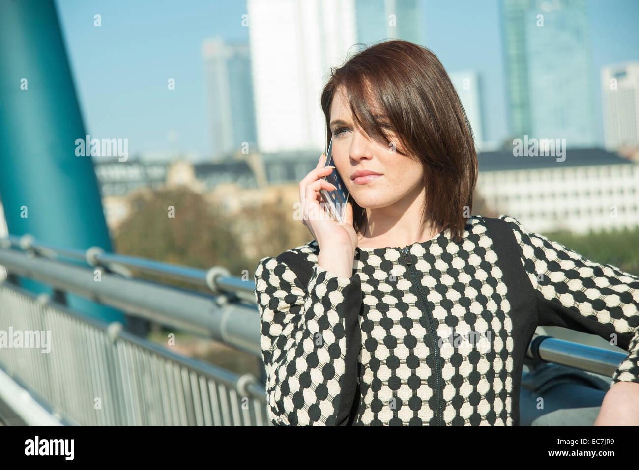 Alemania, Frankfurt, joven empresaria, en el puente sobre el teléfono celular Foto de stock