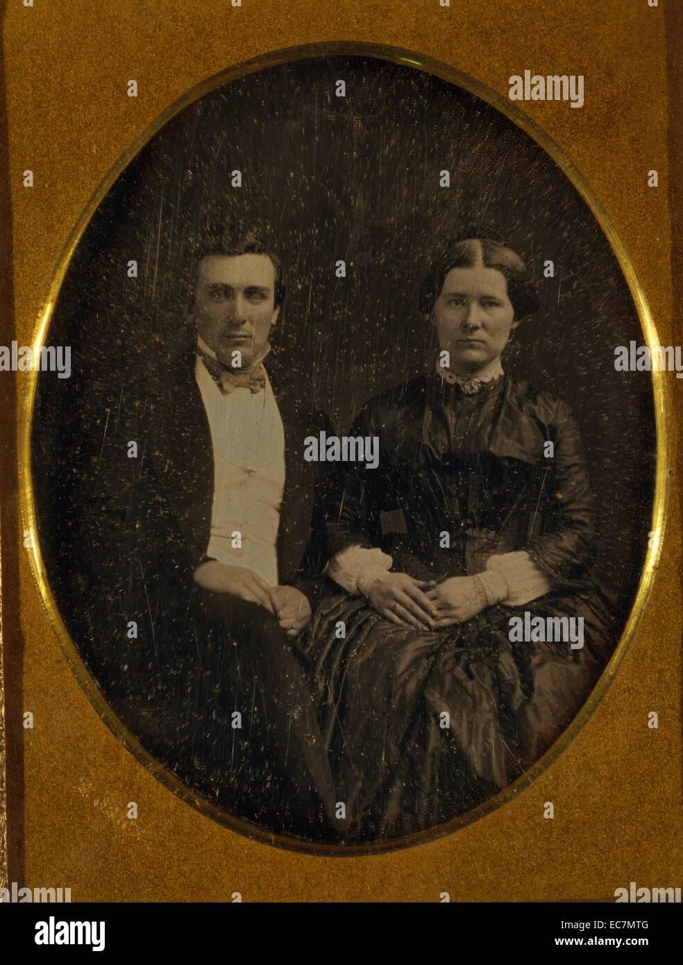 Un hombre y una mujer no identificada, tres cuartas partes de longitud vertical, sentado Imagen De Stock