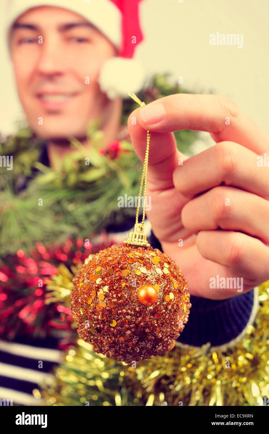 Un hombre joven llevando un gorro de Papá Noel cubierto con adornos de navidad y sosteniendo una bola en su Imagen De Stock