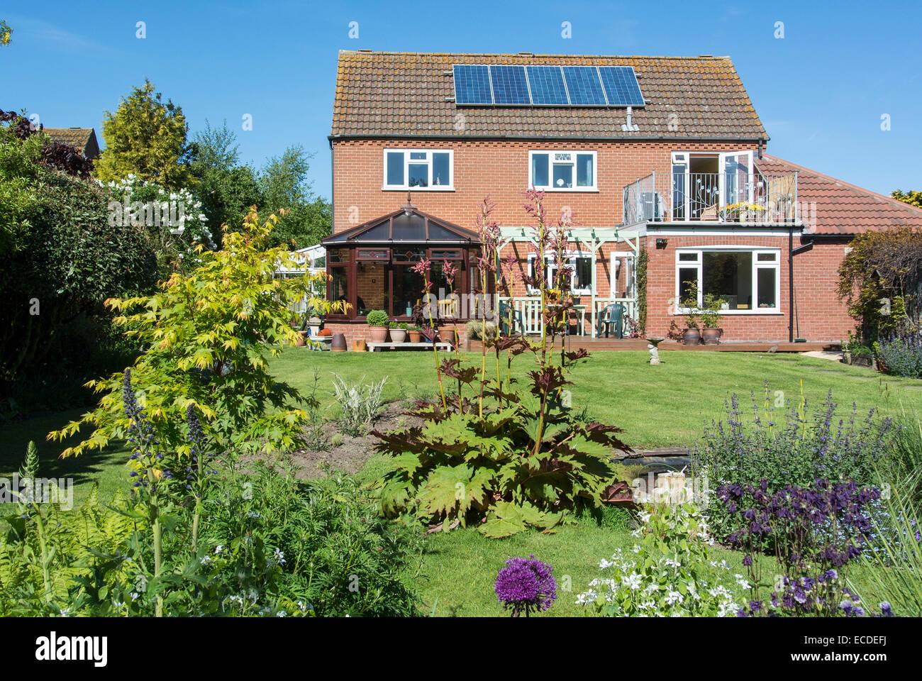 Moderna casa unifamiliar con jardín atractivo y paneles solares Imagen De Stock