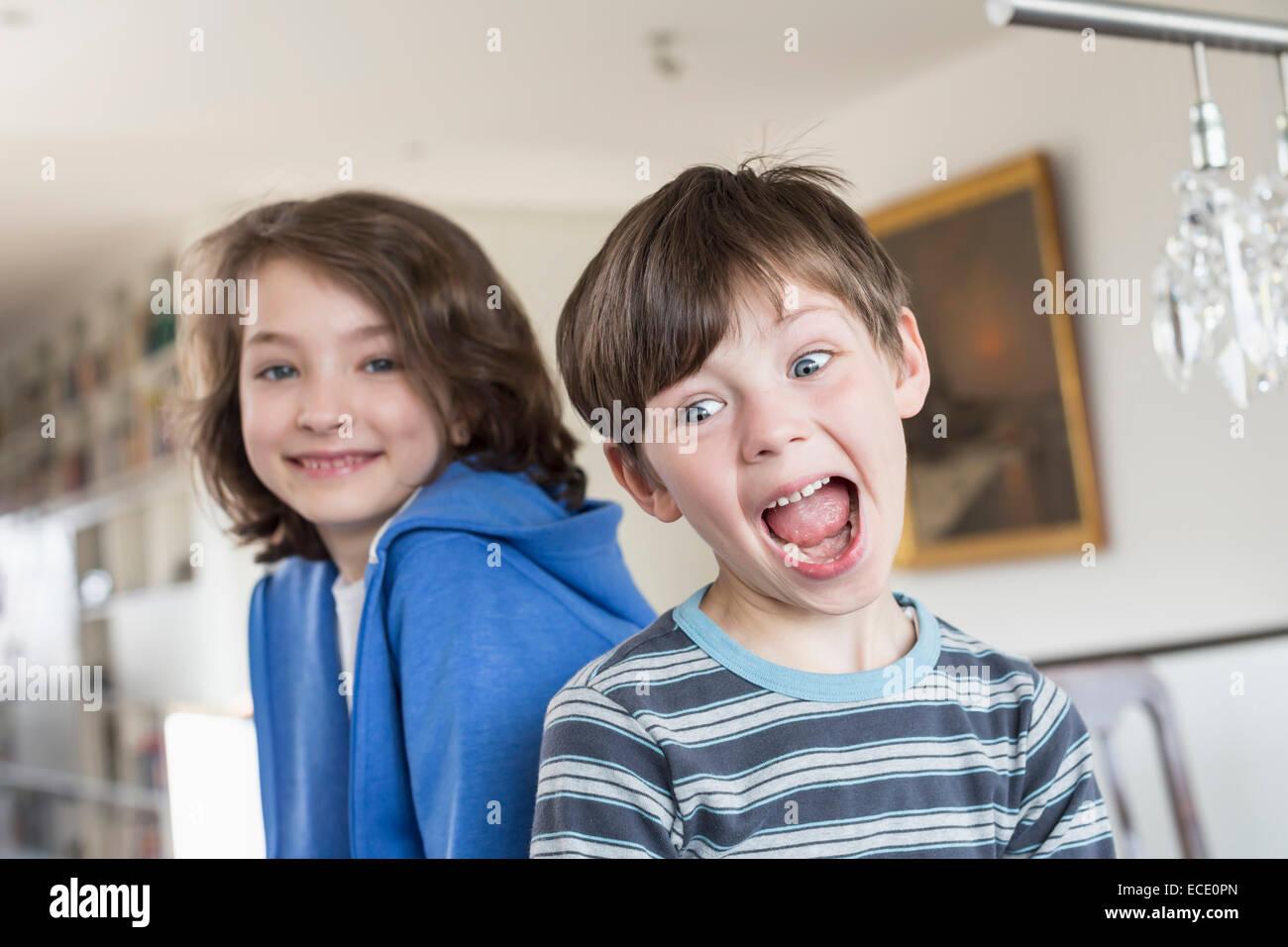 Niño haciendo muecas mientras chica en segundo plano. Imagen De Stock