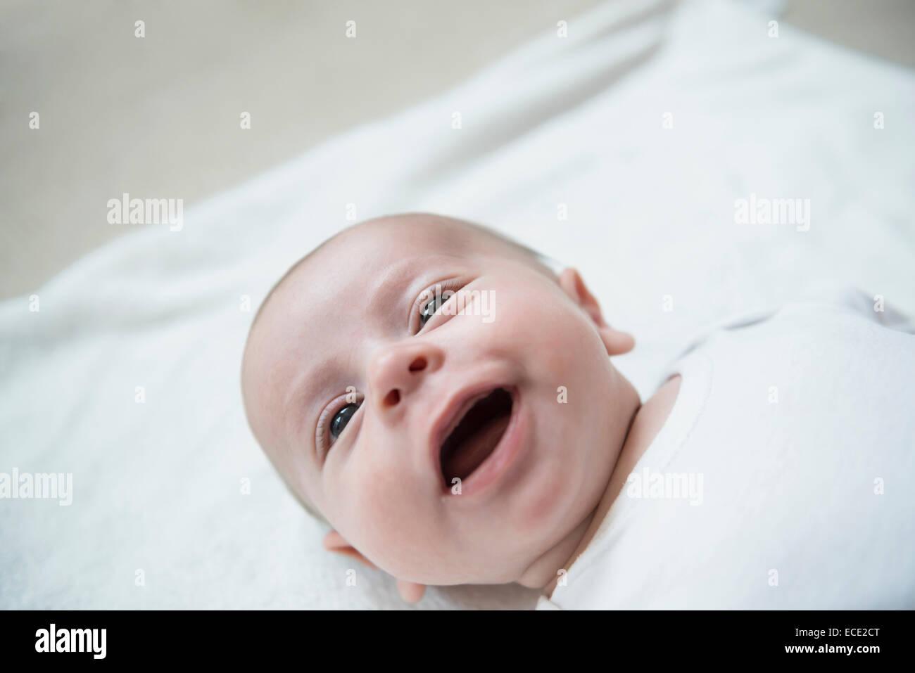 Baby Boy tumbado en la cama, sonriente Imagen De Stock