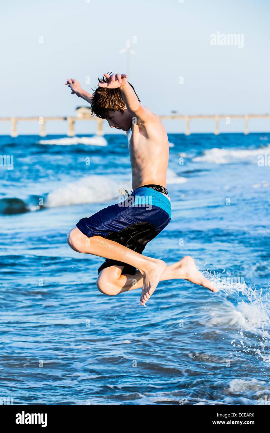 Pelirroja boy en la playa saltando en el surf Imagen De Stock