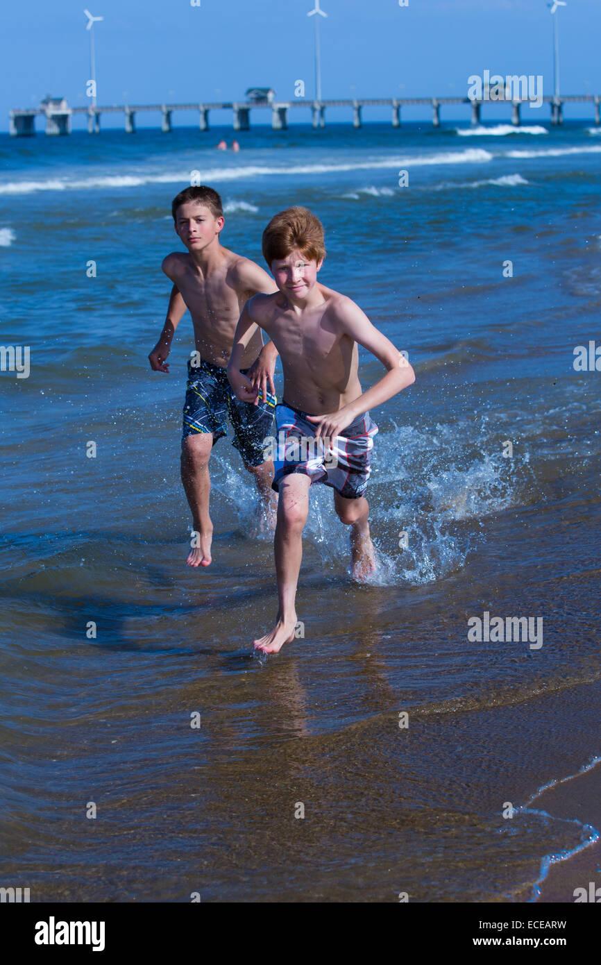 Dos niños corren a lo largo de playa Imagen De Stock