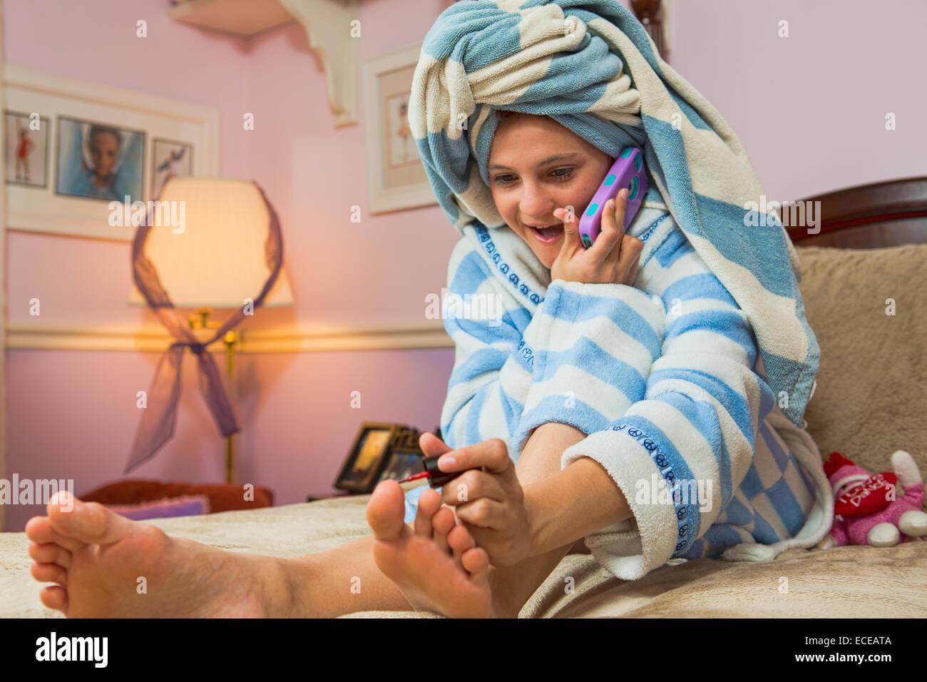 Chica sentada en la cama hablando por teléfono móvil mientras pintar uñas Imagen De Stock