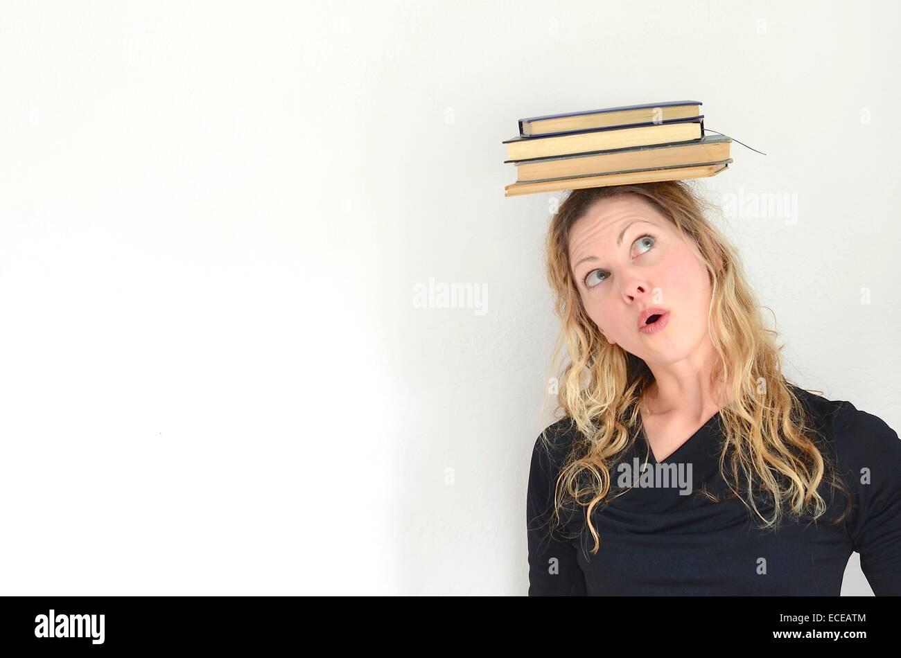 Mujer mirando hacia arriba en la pila de libros vintage equilibrado en la cabeza. Imagen De Stock