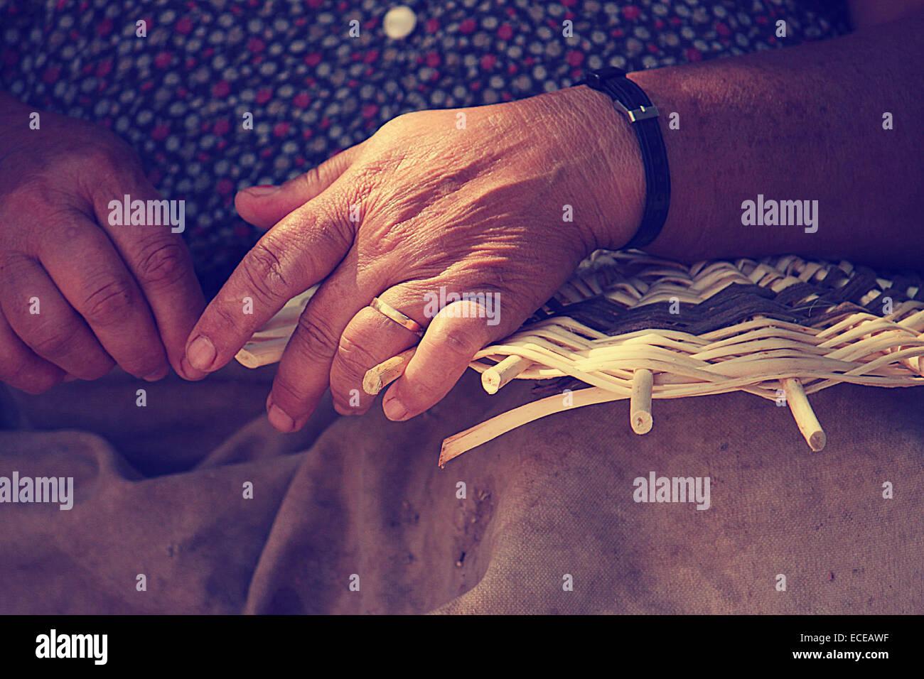 Cerca de manos femeninas, canasta de tejer Imagen De Stock