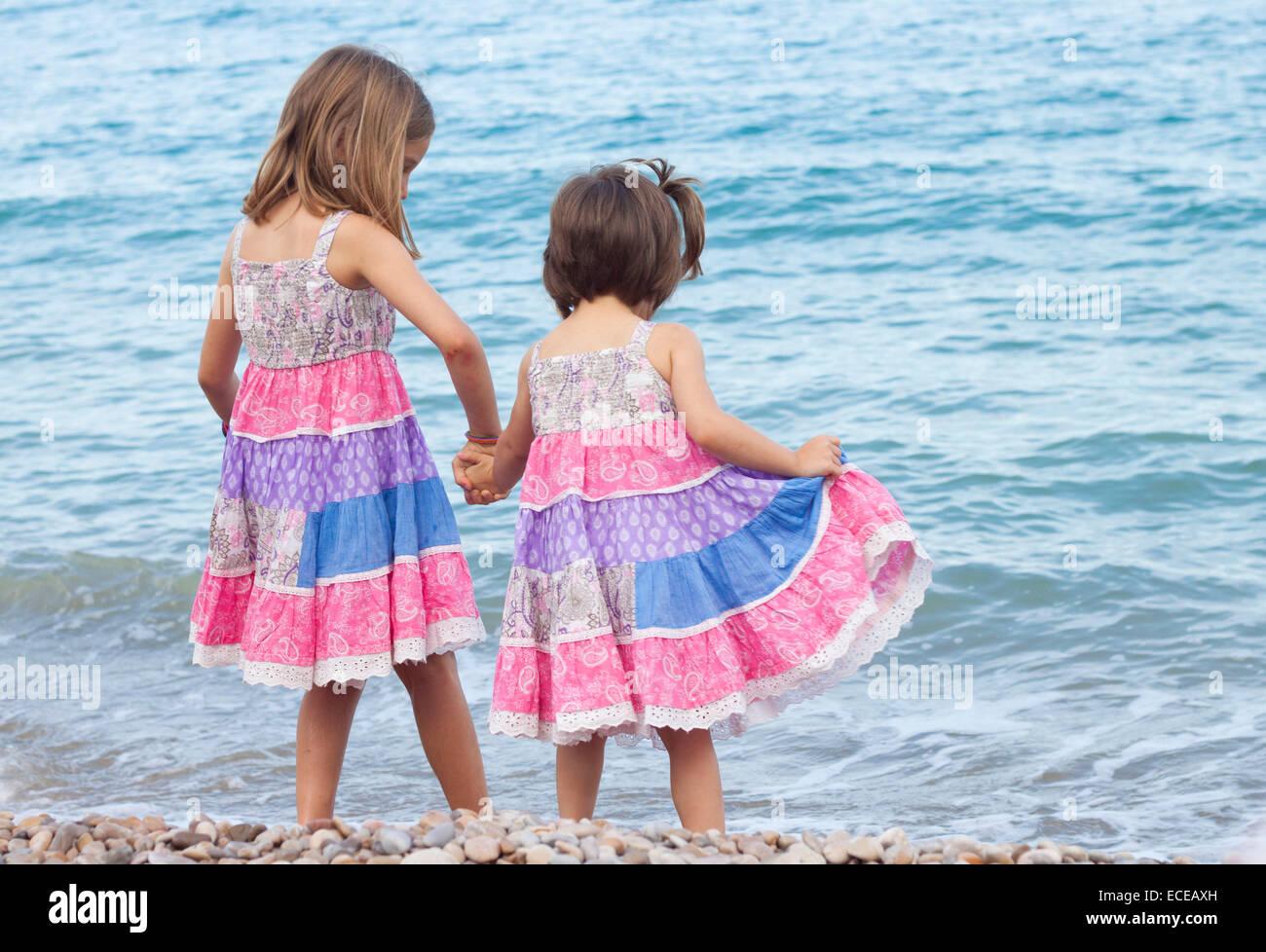 Dos hermanas de pie en la playa, tomados de las manos Imagen De Stock