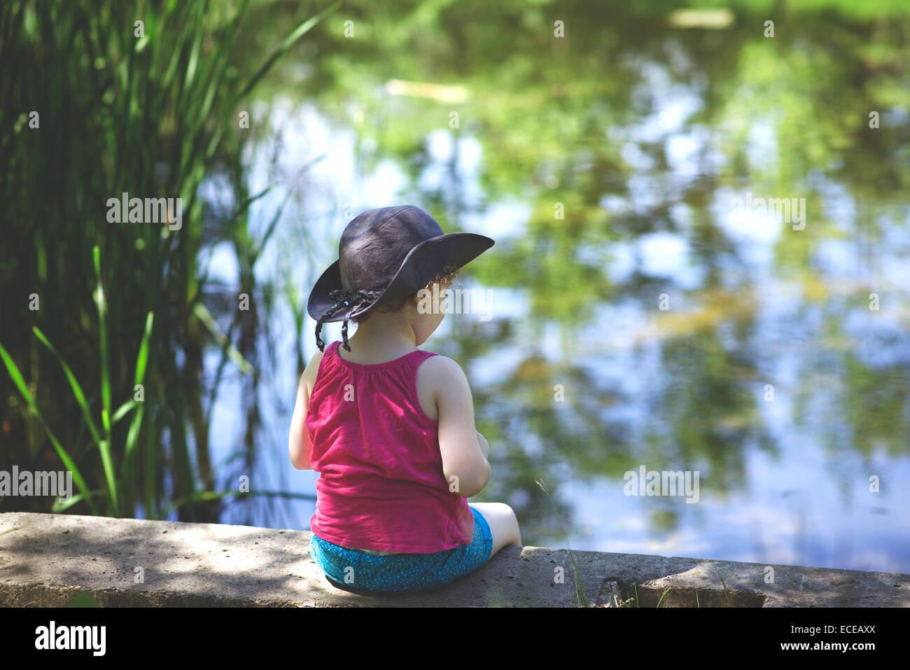 Chica (4-5) sentado al estanque Imagen De Stock