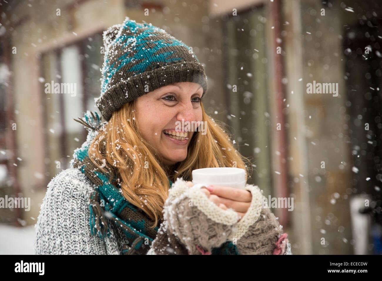 Mujer sosteniendo una taza de té y disfrutar de la nieve Imagen De Stock