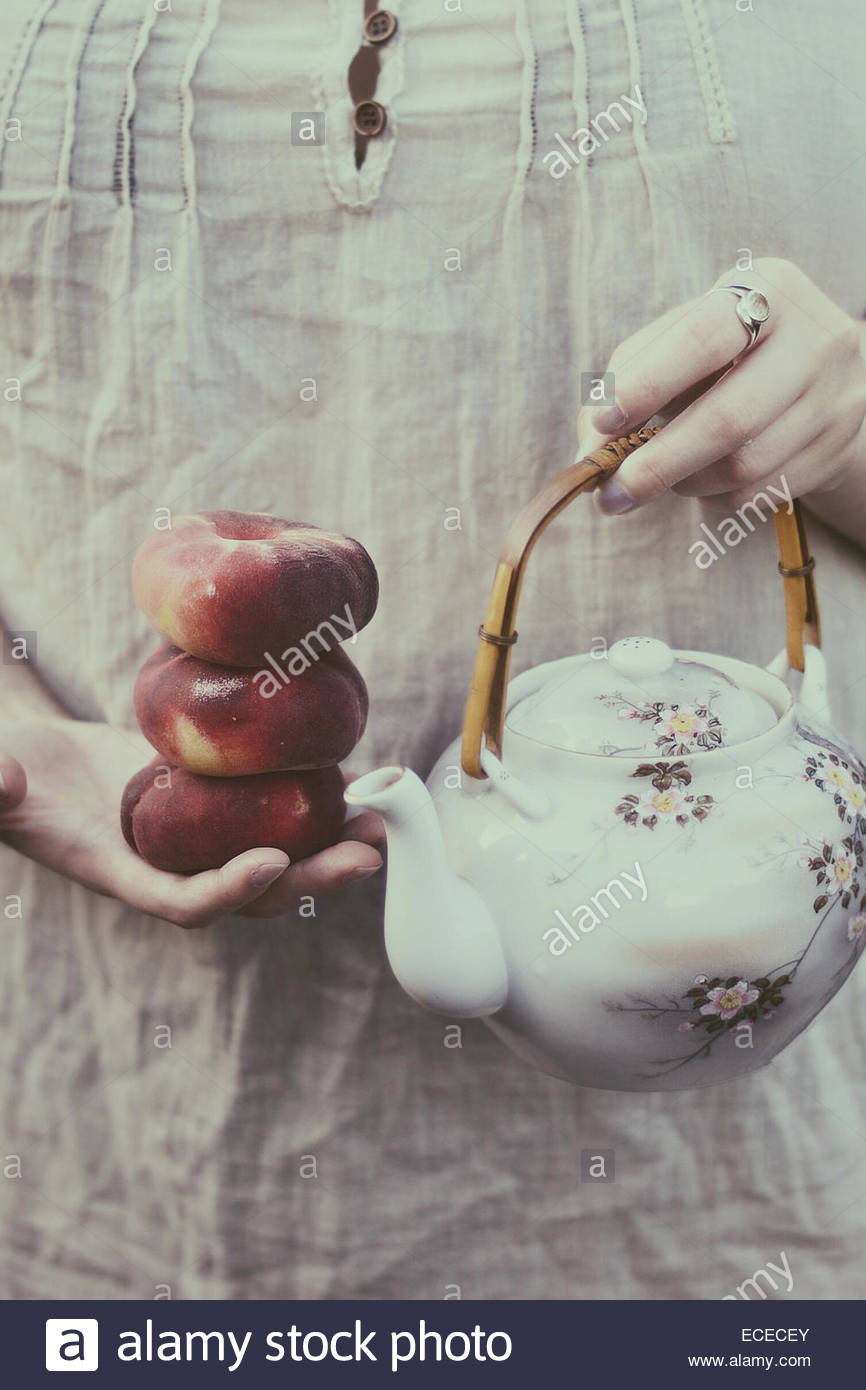 Reino Unido, Inglaterra, Warwickshire, Stratford-upon-Avon, Mujer sosteniendo los melocotones y té oriental Imagen De Stock