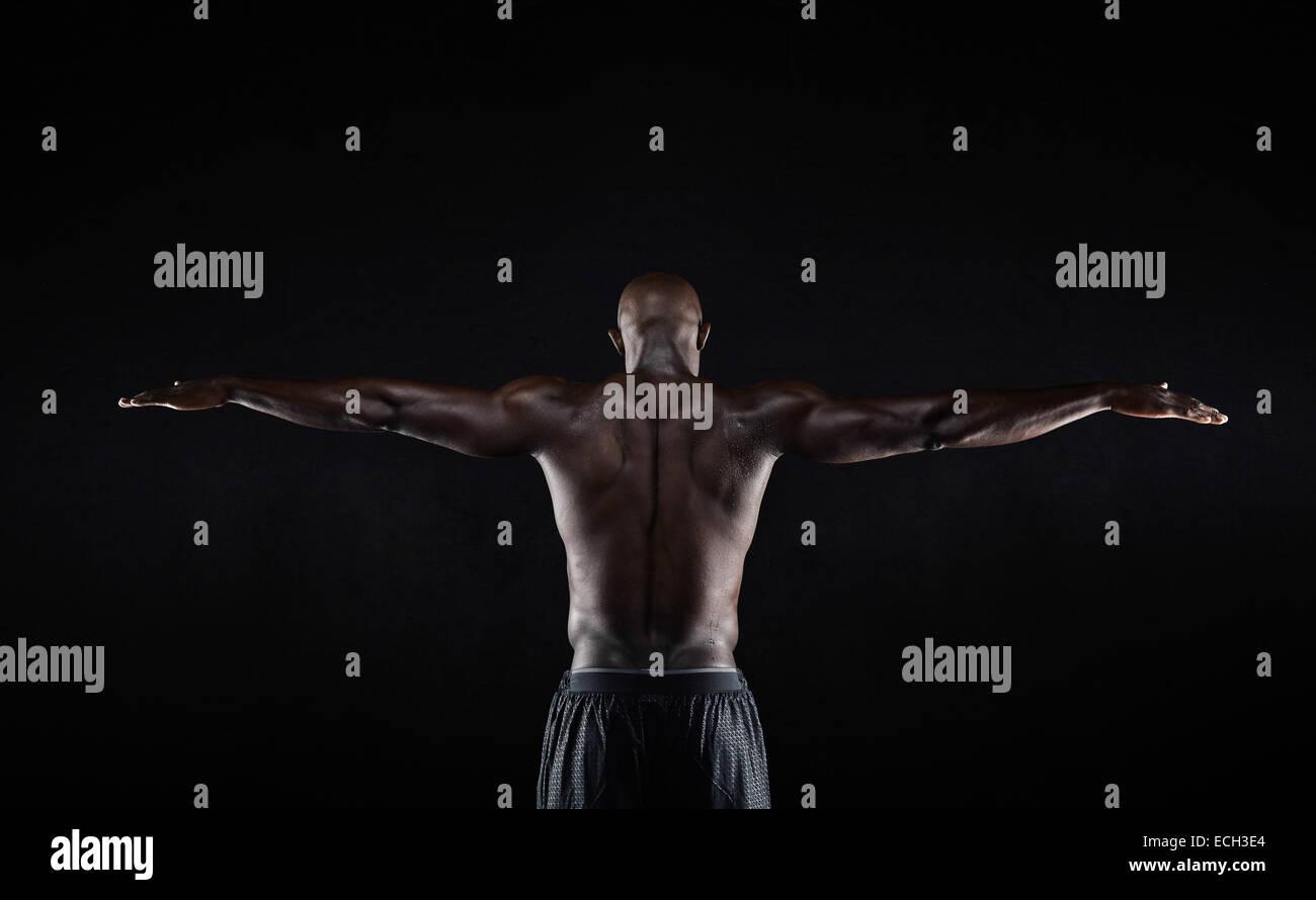 Retrato de una espalda fuerte de un hombre africano estiramiento muscular sus brazos contra el fondo negro. Vista Foto de stock