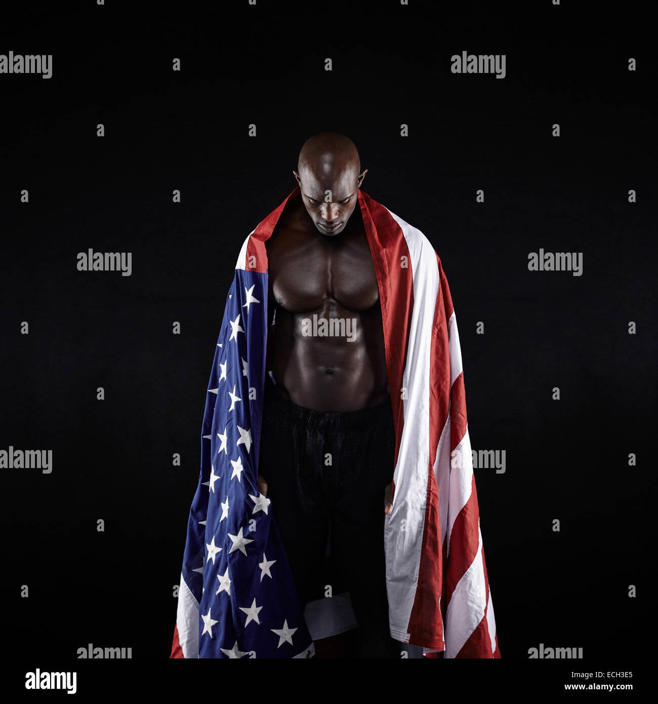 Atleta Masculino que llevaba una bandera Americana contra el fondo negro. Foto de estudio de deportista muscular Imagen De Stock