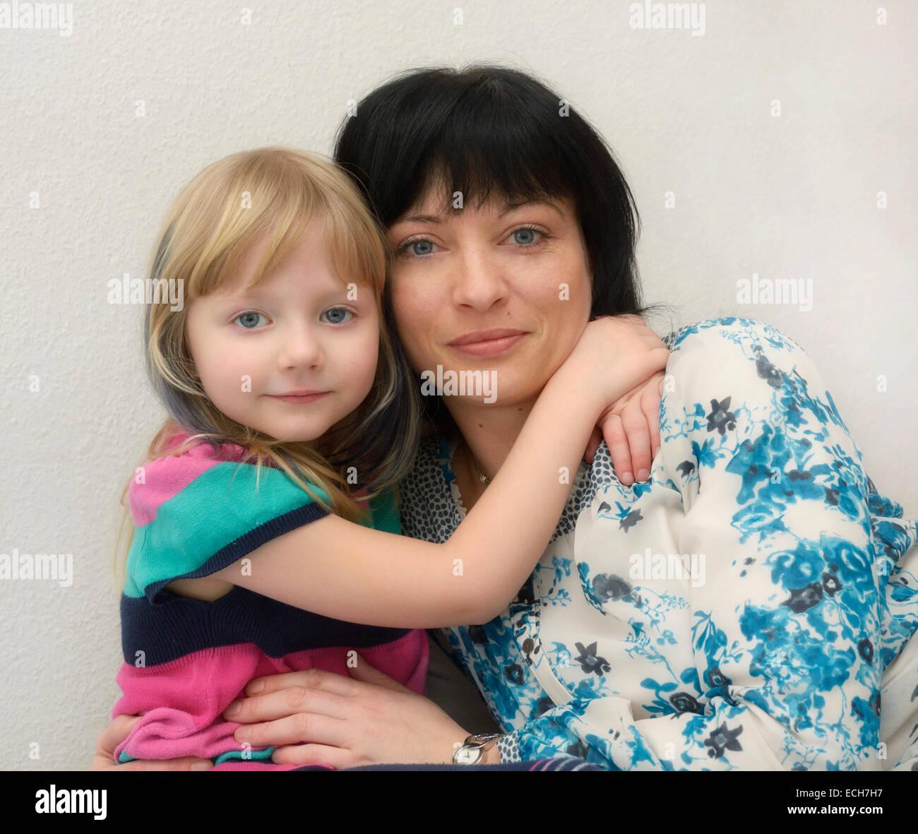 Niña de 5 años, abrazando a su madre, de 35 años Imagen De Stock
