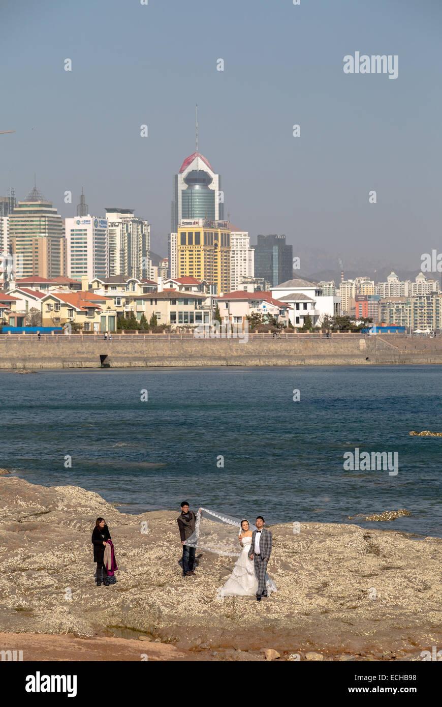 1b37a12232ca2 Nueva pareja tomando la fotografía de bodas en la playa rocosa en Qingdao  Imagen De Stock
