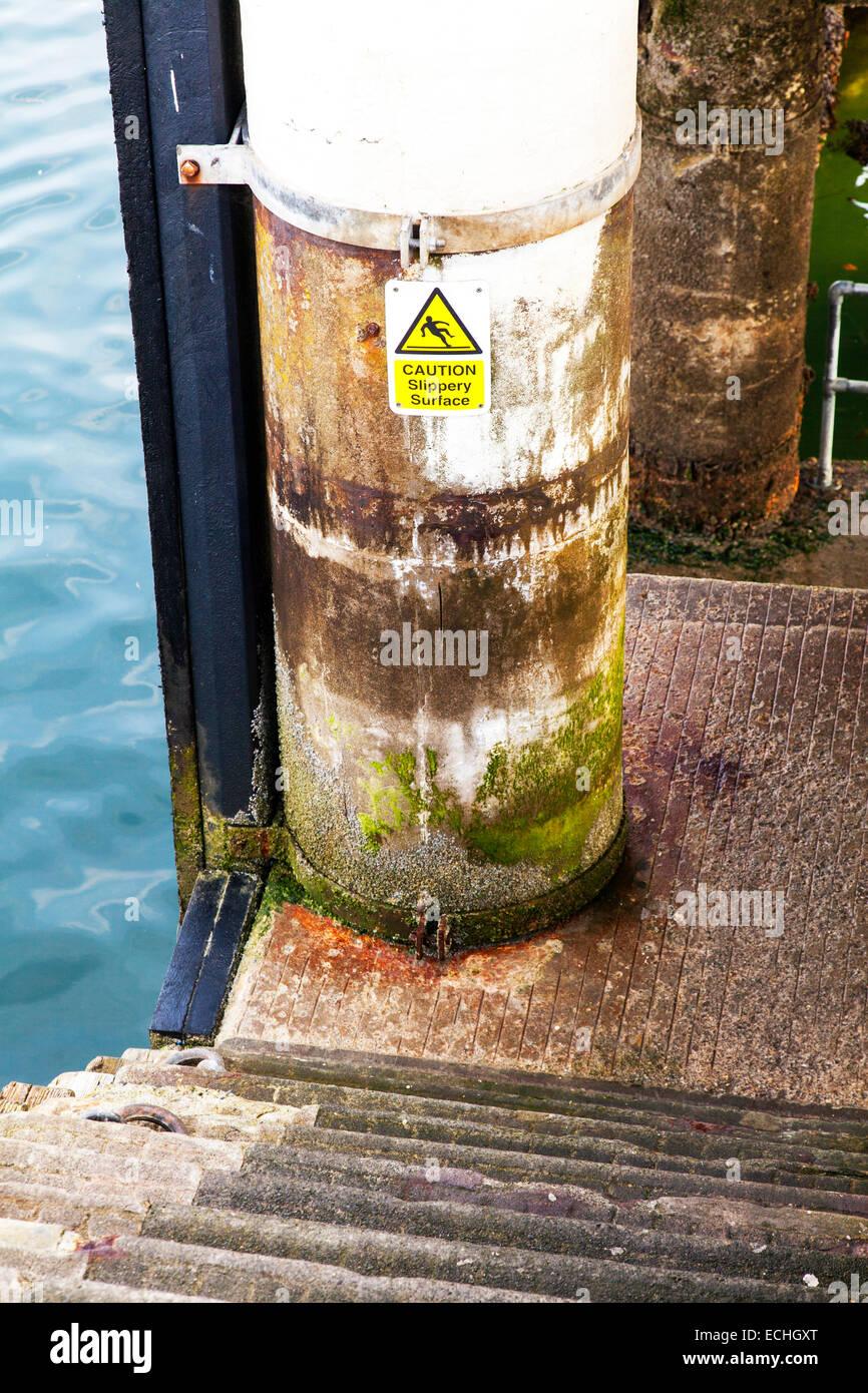 Precaución superficie resbaladiza signo pasos peligro húmedo cieno verde agua el peligro de resbalar abajo Imagen De Stock