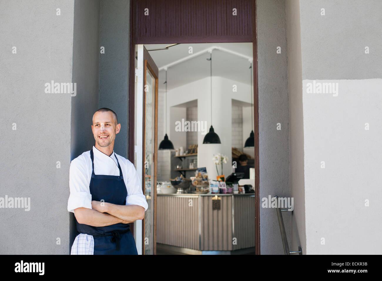 Chef sonriente de pie con los brazos cruzados fuera cocina comercial Imagen De Stock