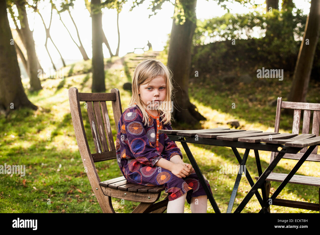 Triste chica sentada en la mesa de madera en el parque Imagen De Stock
