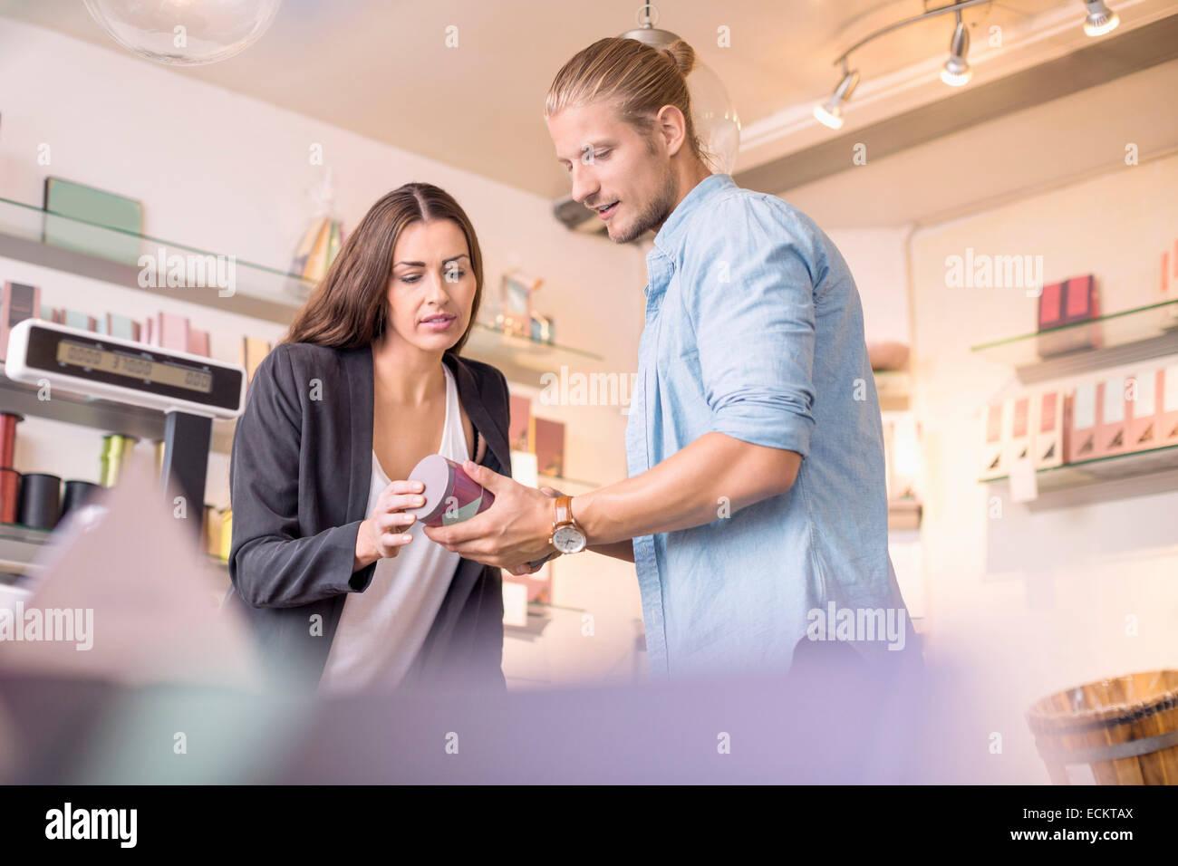 Trabajadora con compañero, discutiendo mientras mantiene el producto en la tienda de dulces Foto de stock