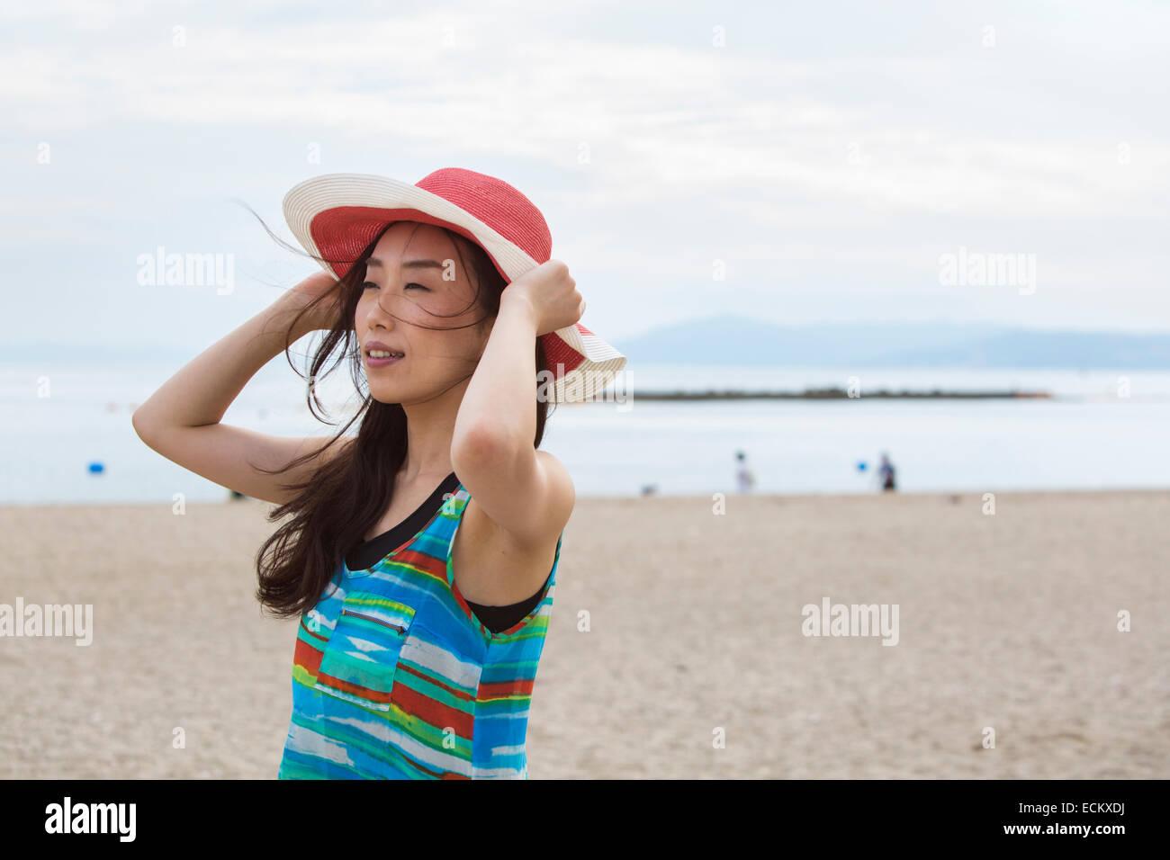 Una mujer en una playa en Kobe, sosteniendo su sombrero. Foto de stock