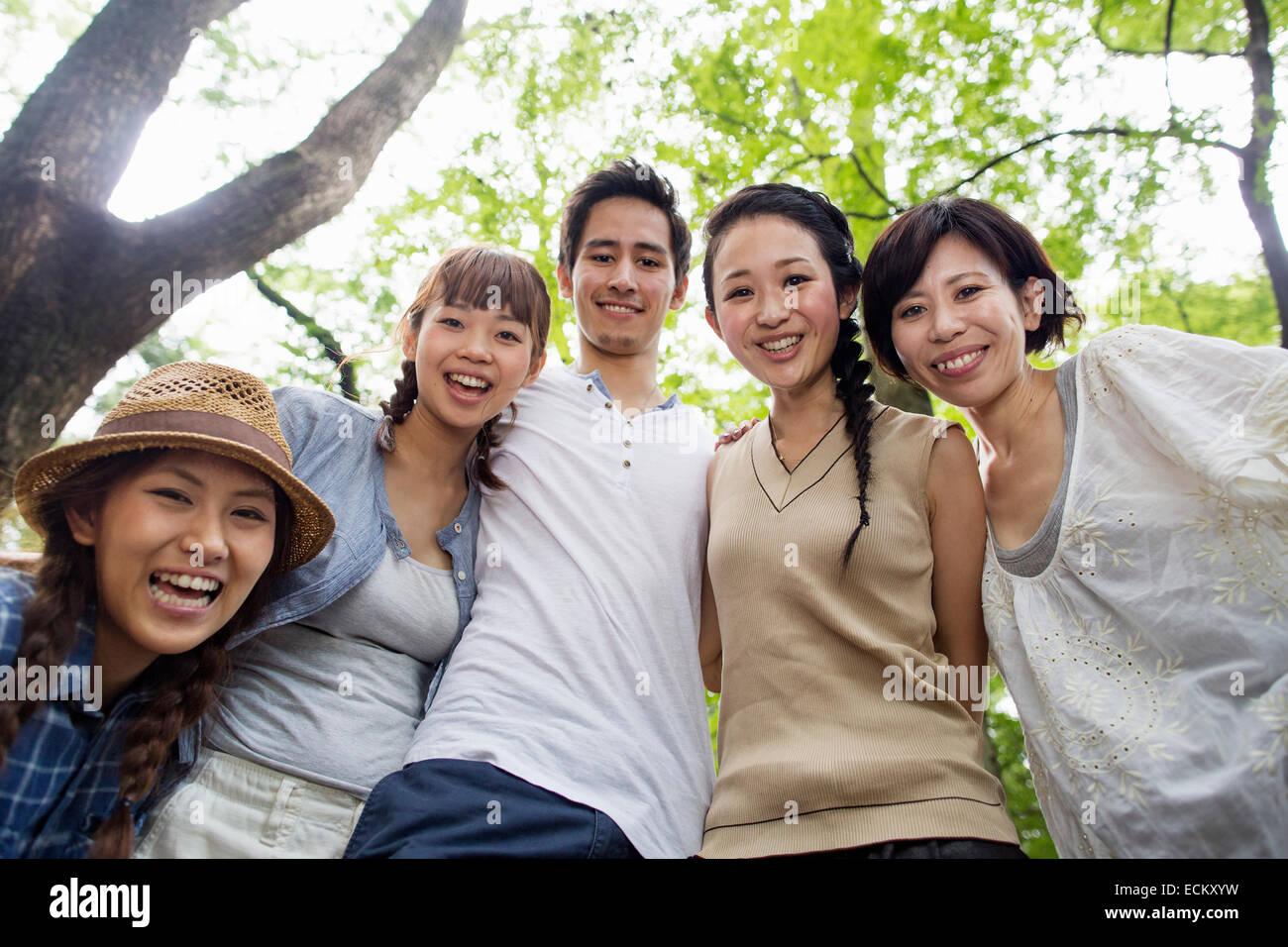 Grupo de amigos a una fiesta al aire libre en un bosque. Imagen De Stock