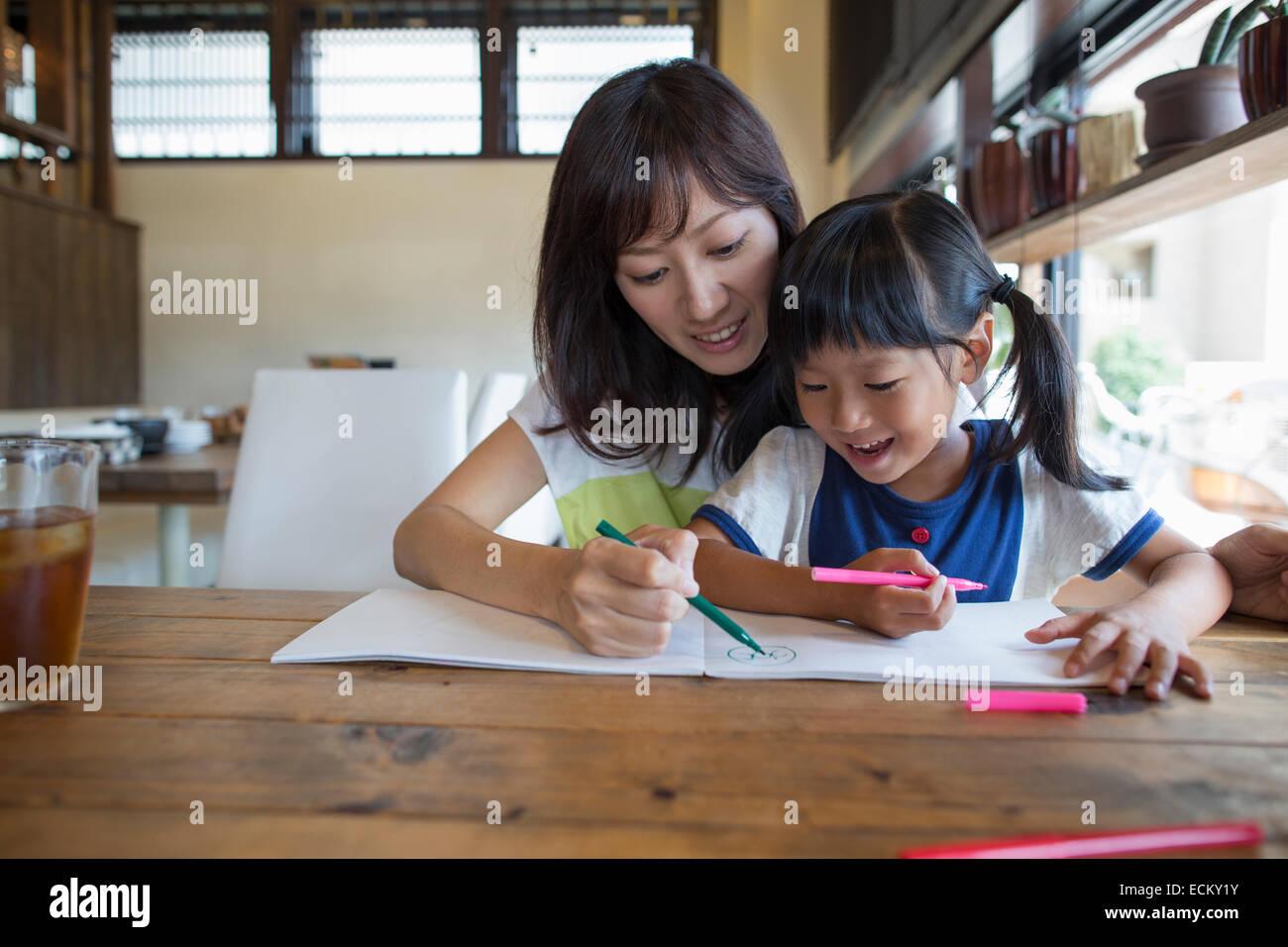 Madre e hija sentadas en una mesa, dibujando con rotuladores, sonriendo. Foto de stock