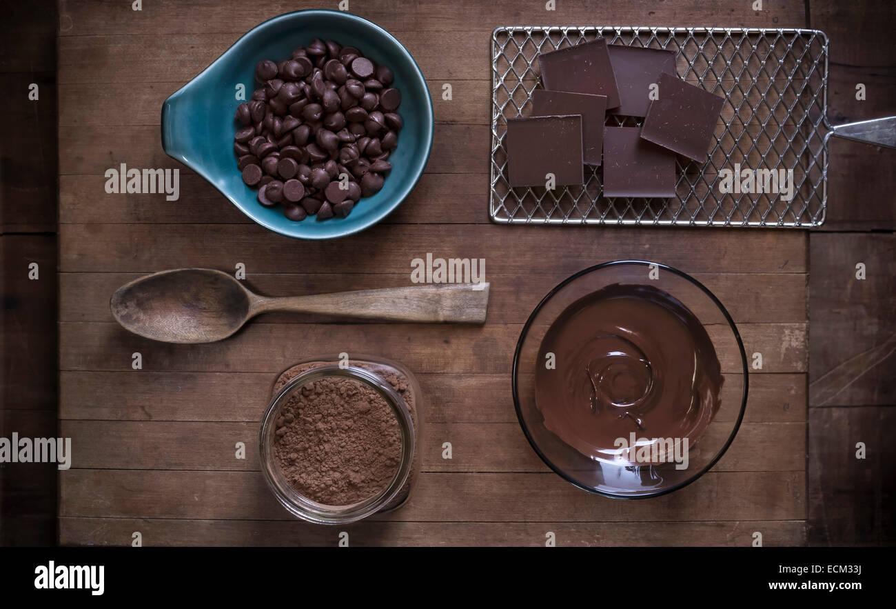 Vista superior de suministros para hornear chocolate dispuestos sobre una superficie de madera rústica con Imagen De Stock