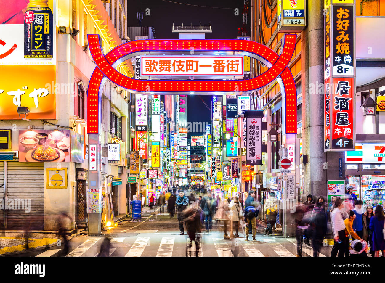 Los peatones caminar bajo signos densamente forrando un callejón en el Kabuki-cho, Tokio, Japón. Imagen De Stock