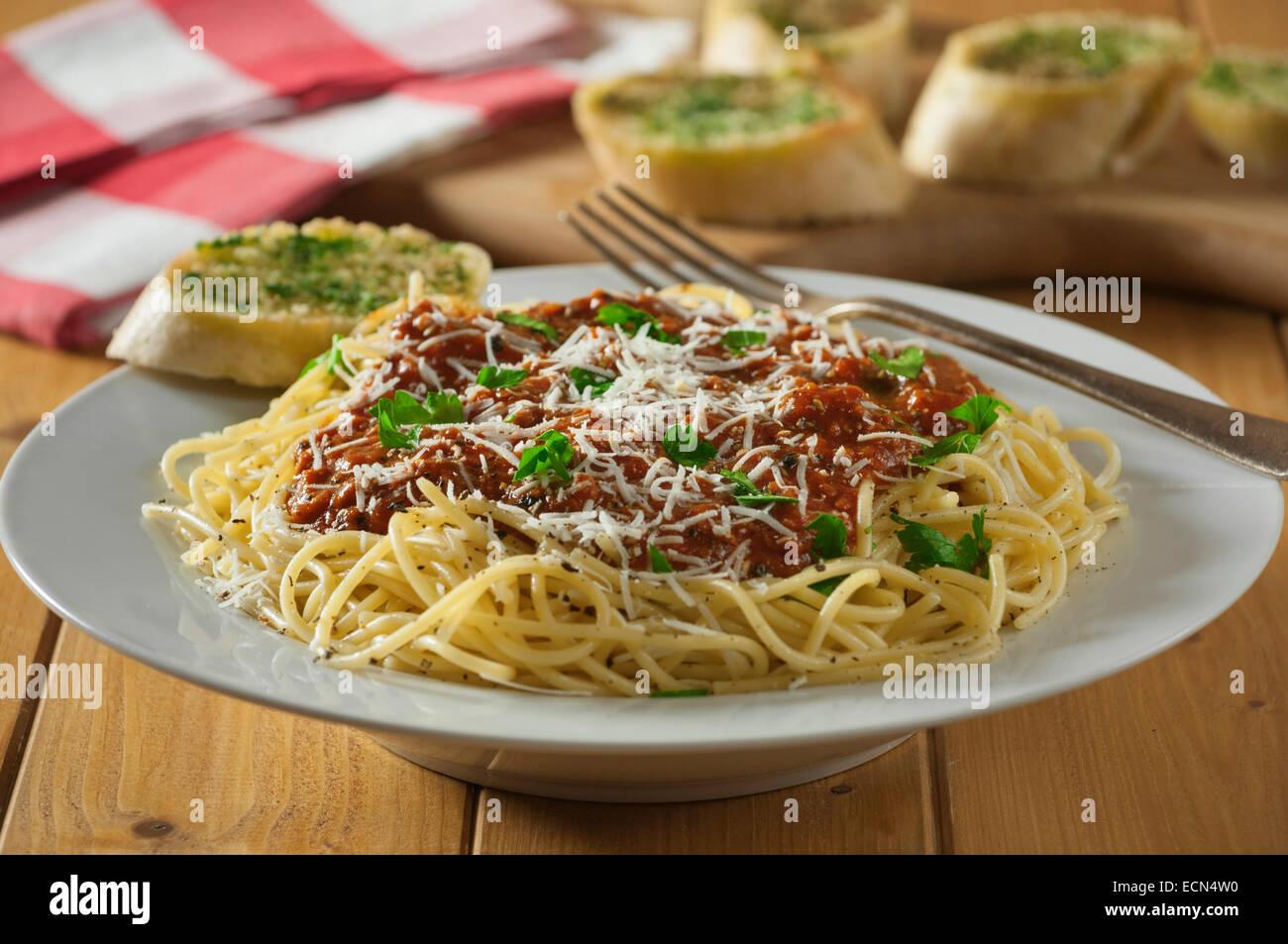 Los espaguetis a la boloñesa con pan de ajo. Plato de pasta italiana. Imagen De Stock