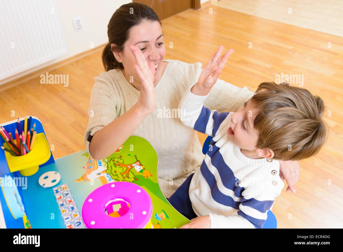 Madre jugando con su hijo cierta creatividad juego y animándole Foto de stock