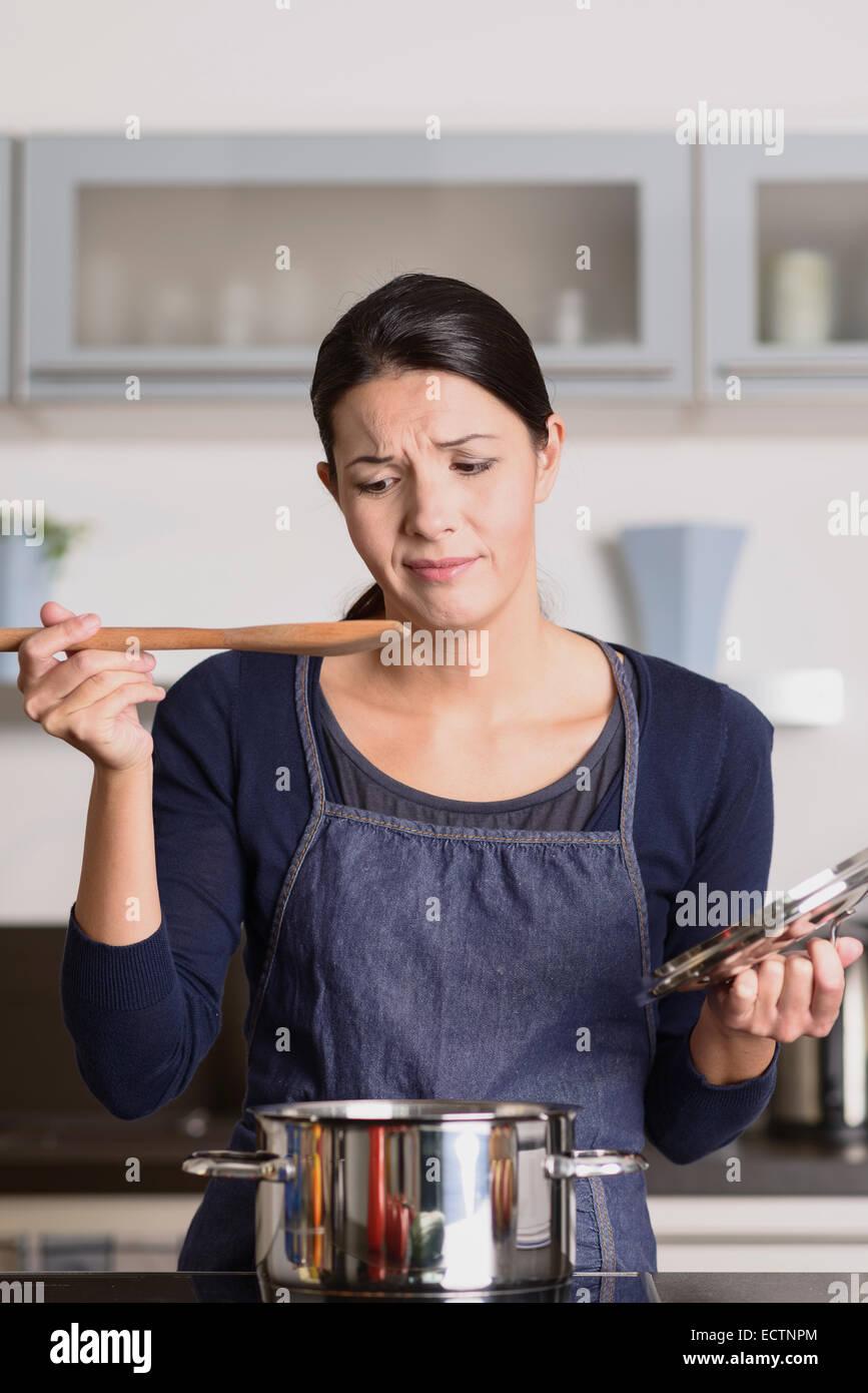Atractiva mujer joven cocinero permanente en la encimera en su delantal, degustando su comida en la cacerola con Imagen De Stock