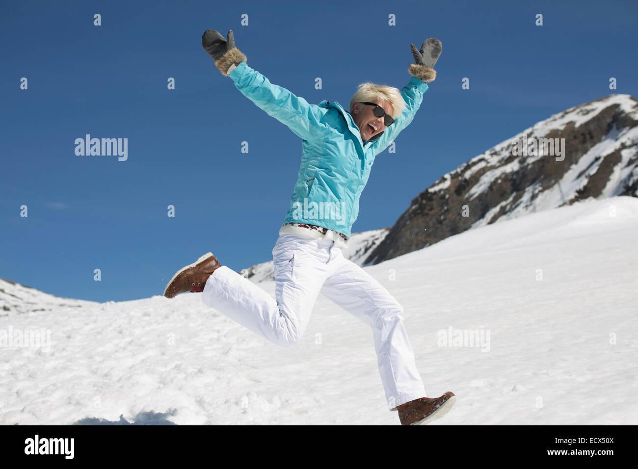 Exuberante mujer jugando en la nieve Foto de stock