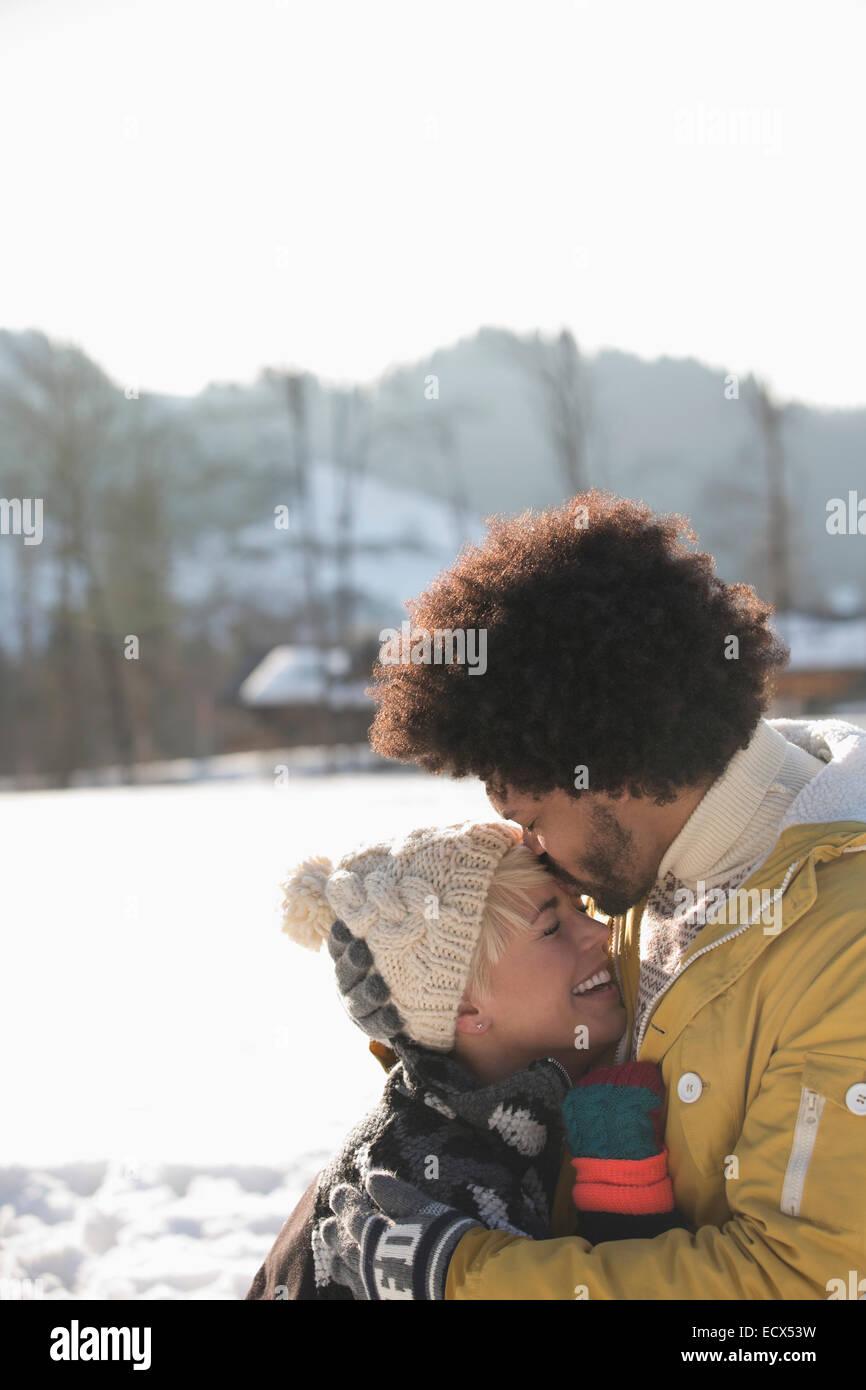 Hombre Mujer beso en la frente en la nieve Imagen De Stock