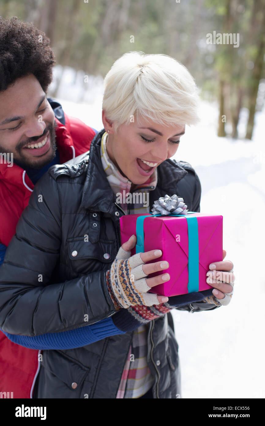 Hombre Mujer sorprendente con su regalo de Navidad en la nieve Imagen De Stock