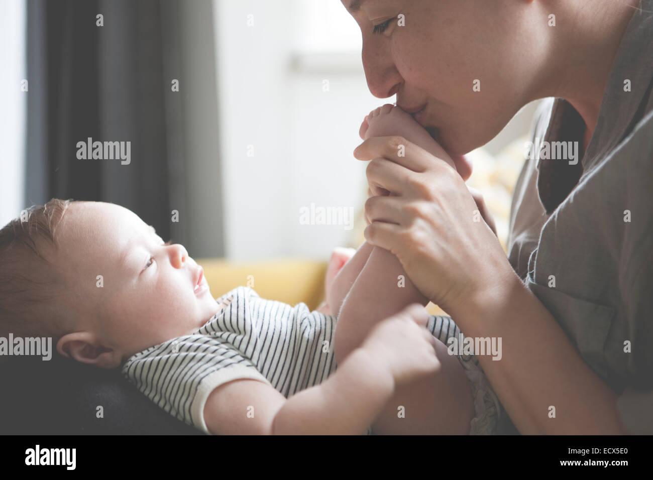 Madre sosteniendo y besarse poco pies del bebé. Imagen De Stock