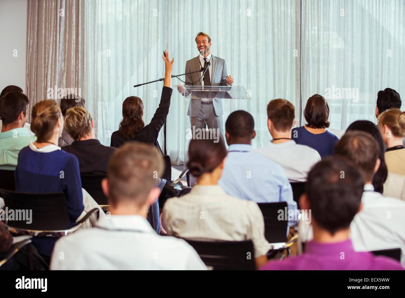 Empresario dando la voz en la sala, una mujer del público levantando la mano Imagen De Stock