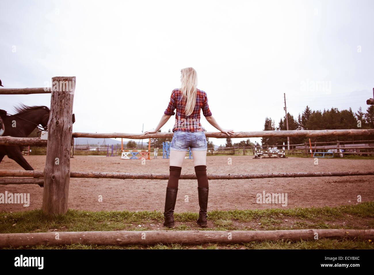 Mujer caucásica viendo caballos en Rancho Foto de stock