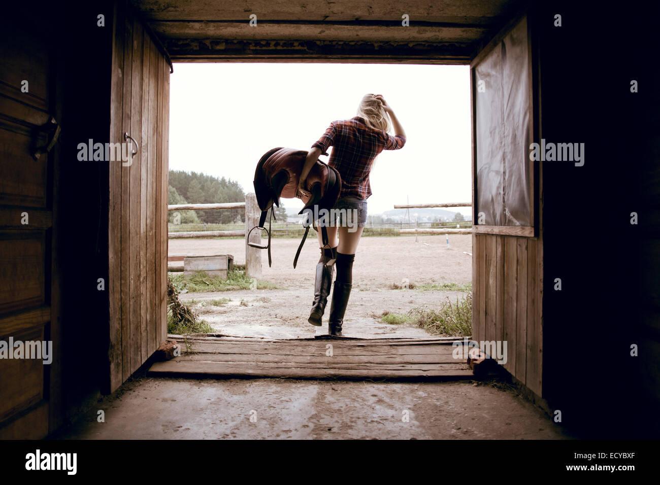 Mujer caucásica llevar silla de caballo en el granero puerta Foto de stock