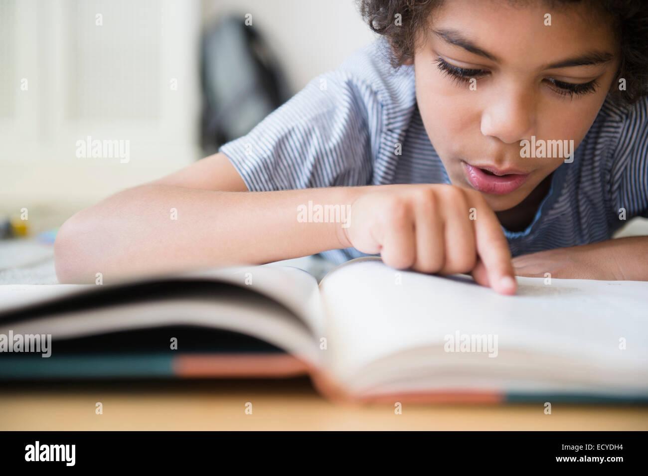 Mestizos boy libro de lectura en la recepción Foto de stock