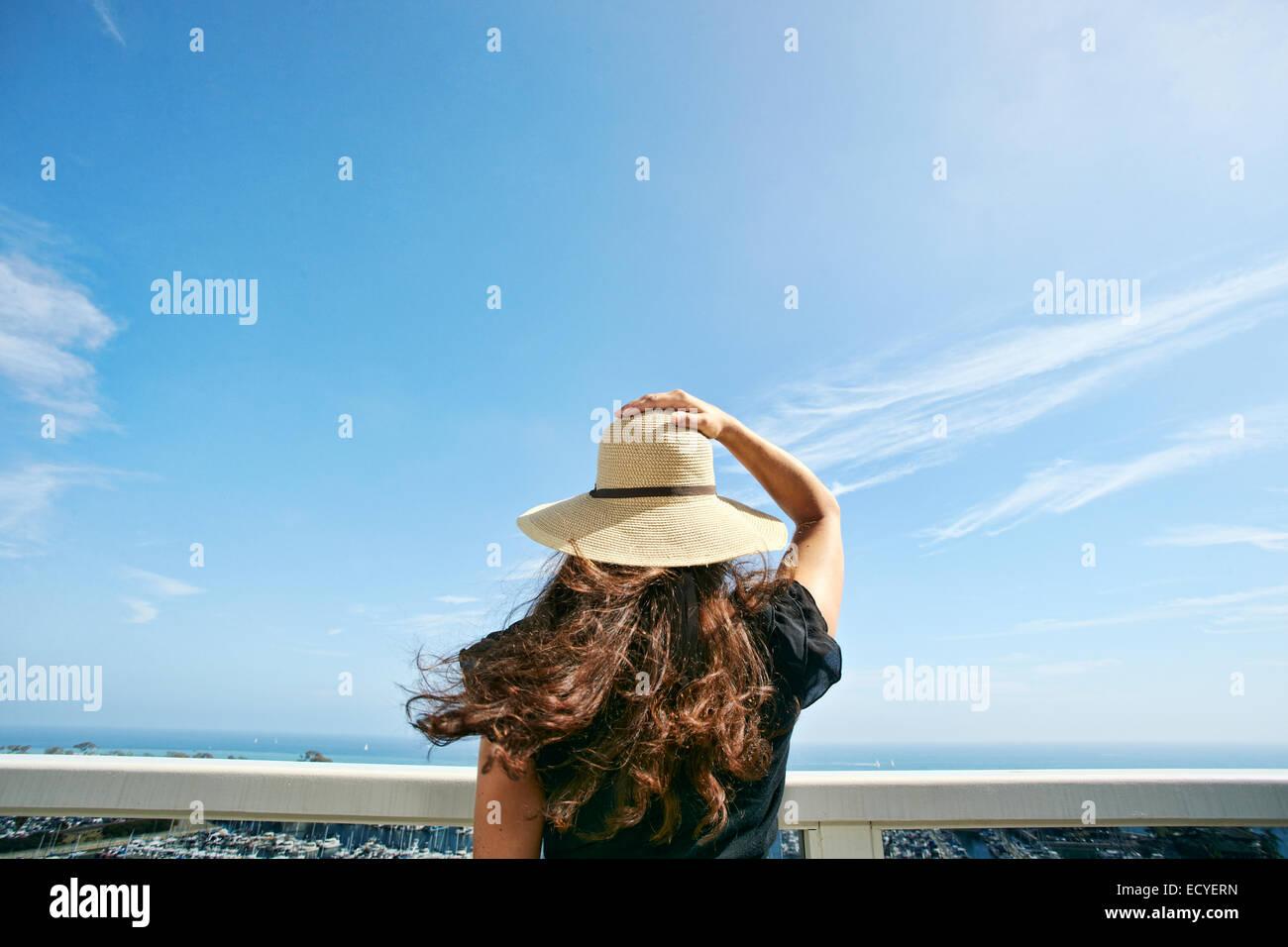 Mujer con sombrero para el sol, admirando vistas panorámicas desde el balcón Foto de stock