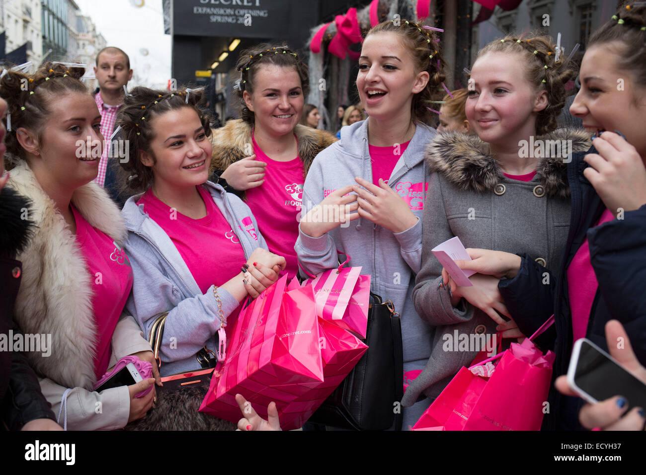 El grupo de niñas con su pelo en rulos y vestidos de rosa. Londres, Reino Unido. Imagen De Stock