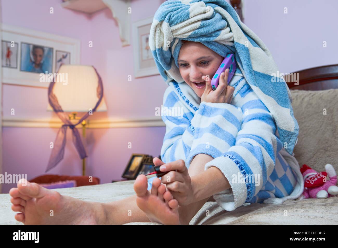 Chica joven hablando por teléfono móvil mientras pintar uñas Imagen De Stock