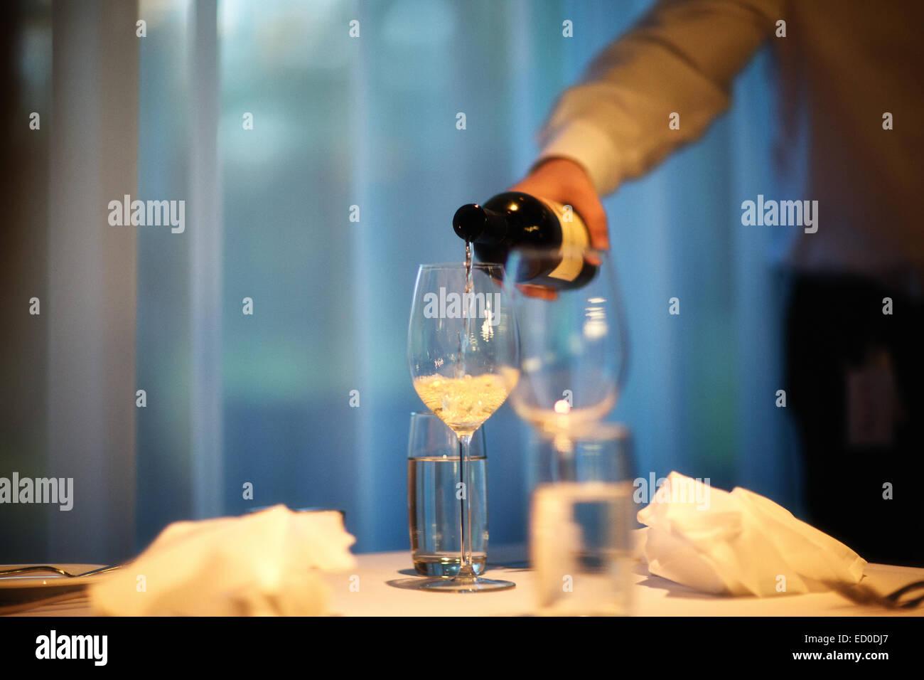Captura recortada del hombre en la habitación vertiendo vino blanco wineglass Imagen De Stock