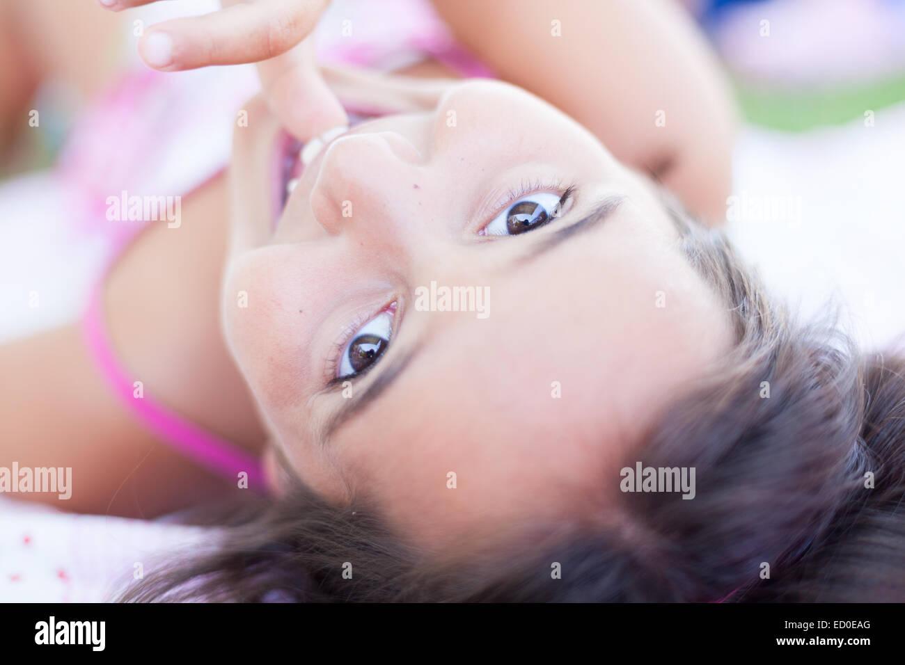 Close-up de chica (6-7) acostado sobre la espalda y mirando a la cámara Imagen De Stock