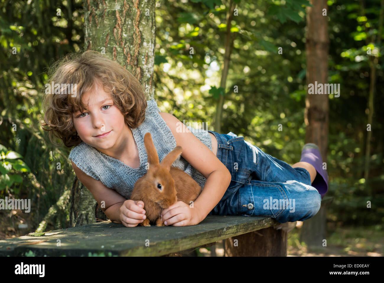 Boy (6-7) la celebración de mascota conejo y acostado en un banco en el bosque Imagen De Stock